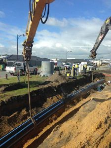 Groundforce Civil employees lowering poly pipe.