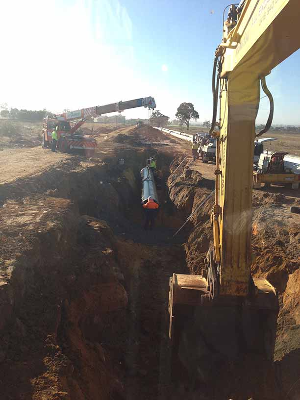 Groundforce Civil employees laying large bore poly pipe into an excavated open trench.