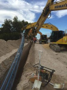 Groundforce Civil employees laying large bore poly pipe into an open trench.